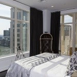 This view of the master bedroom features the armchair along with the large window showcasing the view of the city.