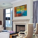 A view of the showcase residence's living room, which focuses more on the painting above the fireplace.