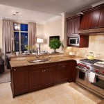 Here's the kitchen of the Laura Hunt showcase residence. It features stainless steel appliances and dark wood cabinets.